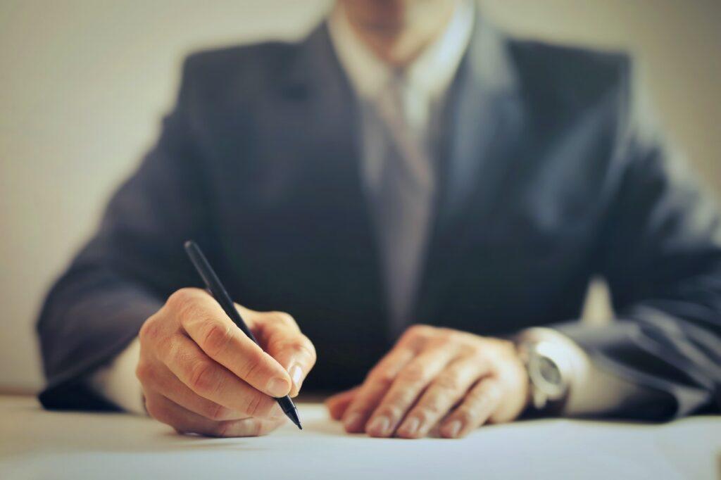 osoba pisząca długopisem